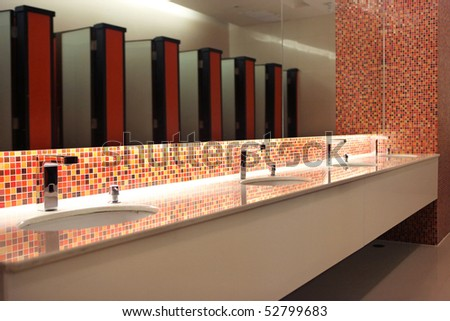 Empty modern restroom interior with washstands and toillets in mirror