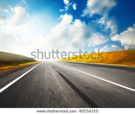 Empty motion blurred asphalt road and blue sky with clouds