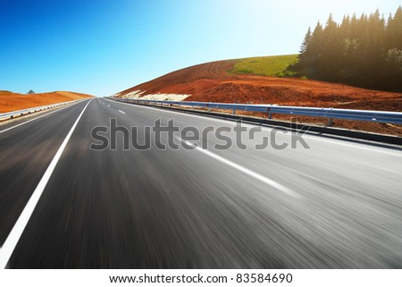 Empty motion blurred asphalt road through hills with red soil and clear blue sky