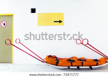 "Empty mountain rescue sled for injured skiers, snowboarders or mountain climbers, danger sign ""STOP!"" and blank yellow caution board in front of white wall background"