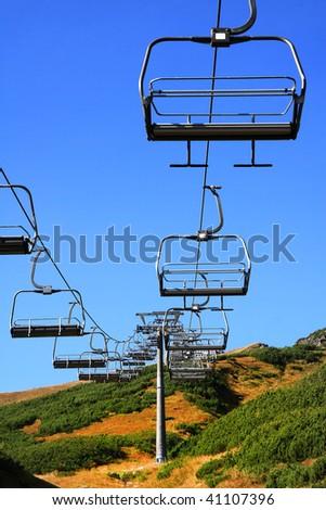 Empty mountain ski chairlift in summer - stock photo