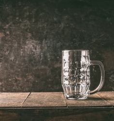 Empty mug of beer  on a rustic table opposite a dark wall, front view.