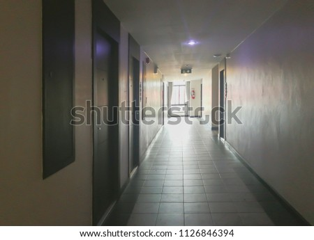 Empty narrow corridor dark and light with doors and wall of downtown department   #1126846394