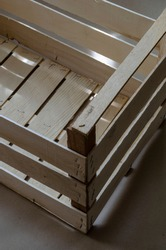 Empty new wooden box made of thin slats. Play of sun and shadow on a wooden box for fruits or vegetables. Eco-friendly packaging for transportation and delivery of products. Top view at an angle