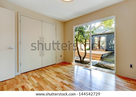 Empty nice room with hardwood floor and large doors.
