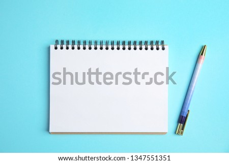 Empty notebook and pen on color background, top view