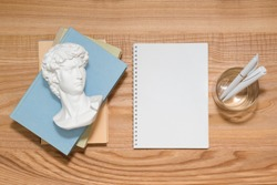 Empty notebook on wooden table with books and small David plaster copy made in China bust sculpture. Top view with copy space, flat lay. Education and art concept. Blank spiral notepad for backdrop