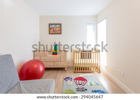 Empty nursery room with a crib, red ball, toys, carpet and couch.