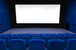Empty of cinema in blue color with white blank screen. Mockup of hall, no people and auditorium