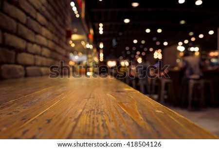Empty of wood counter bar with blur cafe restaurant in dark background/selective focus .For montage product display