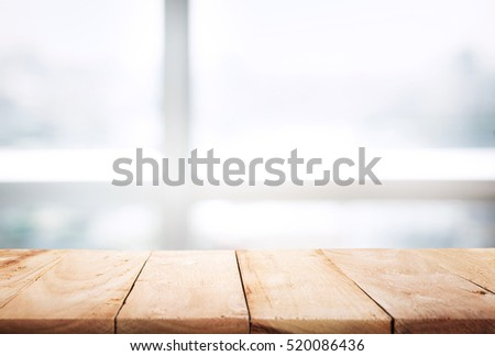 Empty of wood table top on blur of abstract window with sunlight background in winter,Table with window glass in the winter morning background.For montage product display or design key visual layout.