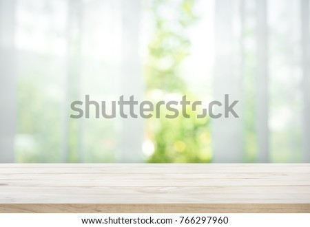 Empty of wood table top on blur of curtain with window view green from tree garden background.For montage product display or design key visual layout #766297960