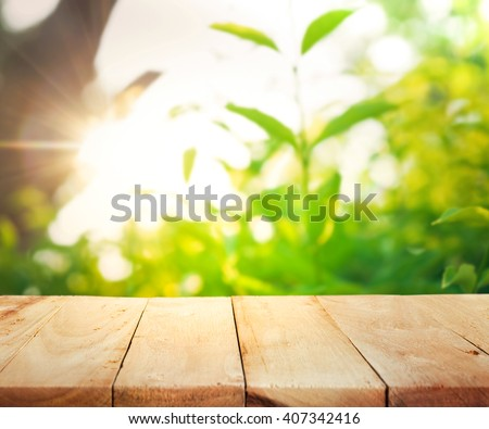 Empty of wood table top on blur of fresh green abstract from garden with sunlight .For montage product display or design key visual layout