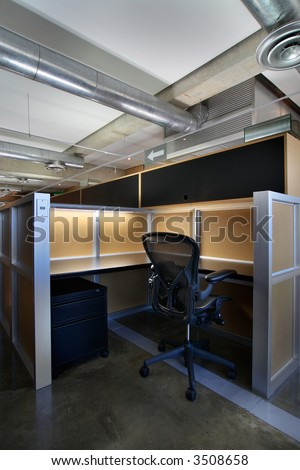 Empty office cubicle in an industrial style office space.