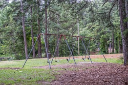 Empty old metal frame with chains holding the rubber seats swing set sitting still in the park in summertime