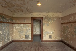 Empty old room in an abandoned building with peeling paint, wood trim and floors