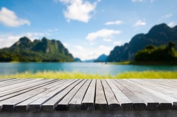 Empty old wooden table in front of blurred background of the lake, mountain, blue sky among bright sunlight on a clear day. Can be used for display or montage for show your products.