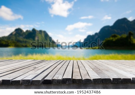 Empty old wooden table in front of blurred background of the lake, mountain, blue sky among bright sunlight on a clear day. Can be used for display or montage for show your products. Сток-фото ©