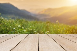 Empty old wooden table in front of blurred view on top of mountains and green field with beautiful sunset background of nature. Can be used for display or montage for show your products.