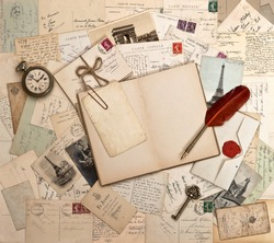 empty open book, old accessories and post cards. sentimental vintage background