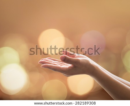 Empty open hands with palms up and candle lights bokeh in warm gold color tone: Female prayer praying warm tone background: Peace of mind mental health concept: Humanity aid: Easter Holy spirit week