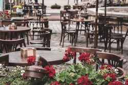 Empty outdoor cafe during quarantine, filtered. Restaurant terrace with tables and chairs, toned image. Street cafe with flowers. Elegant street cafe. Outdoor bistro furniture. Cozy patio background.