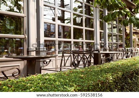 Empty outdoor cafe - metal forged furniture fenced by green hedge. Tables and chairs at restaurant terrace #592538156