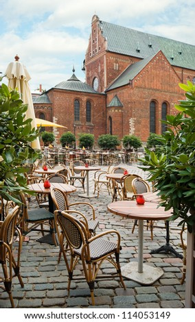 Empty outdoor cafe on the background of the Dome Cathedral in Riga, Latvia