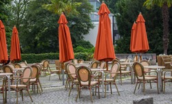 Empty outdoor cafe with closed umbrellas. Street cafe with empty tables and chairs. Restaurant furniture concept. European cafe in summer patio. Summer terrace with tables and free seats.