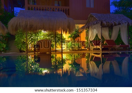 Empty outdoor swimming pool with deck chairs illuminated by warm light. Night time.