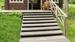 Empty outdoor wooden staircase steps in front of the cottage house against the background of green grass, close up bottom up view on a summer day, Russian natural landscape