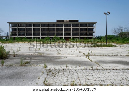 Empty overgrown parking lot and abandoned  former hospital building  Tinley Park Illinois stock photo