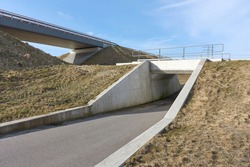 Empty overpass for cars and underpass for cyclists and pedestrians under a blue sky in early spring.