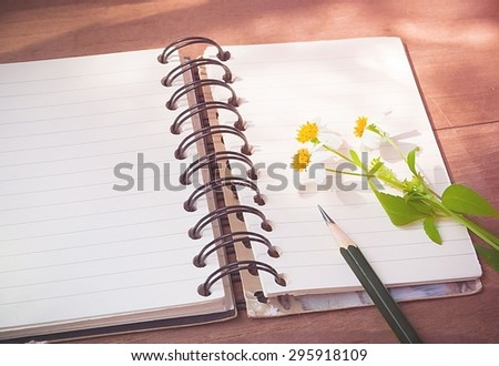 Empty page of notebook on desk, Black pencil and flower on notebook, Space for text, Vintage style