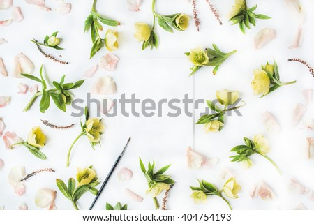 Empty paper blank with pink roses petals, yellow flowers and paint brush on white background. Flat lay, top view