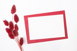 Empty paper card mock-up on the table with dry red flowers, top view