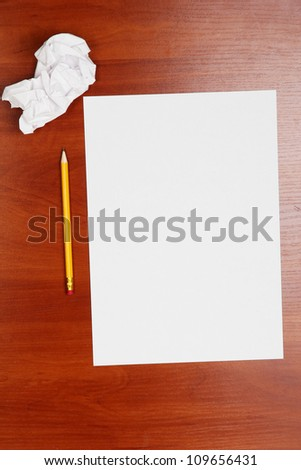 empty paper, crumpled paper and pencil on wooden table