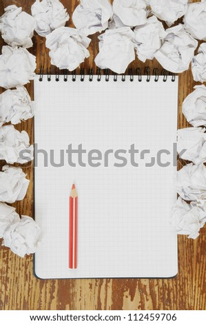 Empty paper, crumpled paper and red pencil on wooden table
