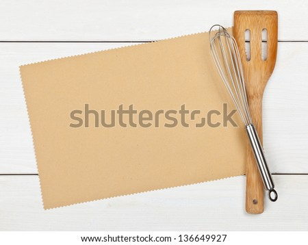 Empty paper for recipe with cooking utensils on kitchen table
