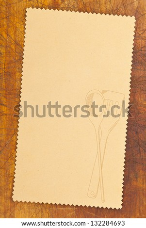 Empty paper for recipe with drawn cooking utensils on kitchen table