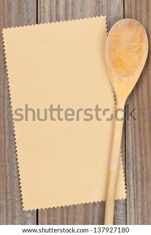 Empty paper for recipe with wooden cooking utensils on kitchen table