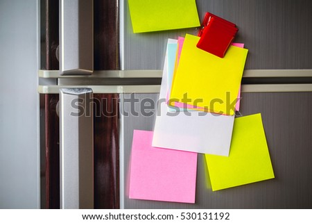 Empty paper sheet on refrigerator door with magnetic clip paper note for add text message. #530131192