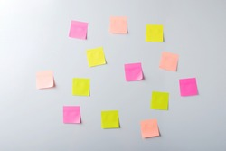 Empty paper stickers of pastel shades hang on light wall. Front view of chaotically arranged notes.