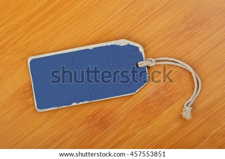 Empty paper tag on wickered wooden background #457553851