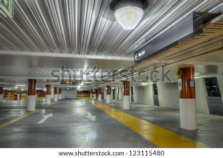 Empty parking interior at night, brightly lit, with red and white columns and yellow pedestrian walkway.