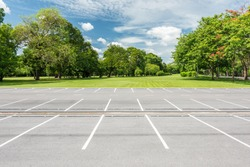 Empty parking lot against green lawn in city park