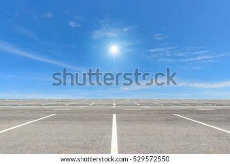 Empty parking lot on blue sky and sun reflection #529572550