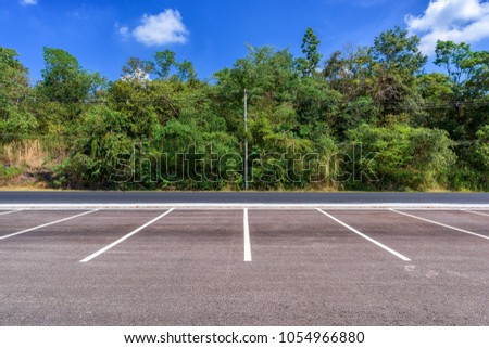 Empty parking lot with forest and beautiful blue sky. #1054966880