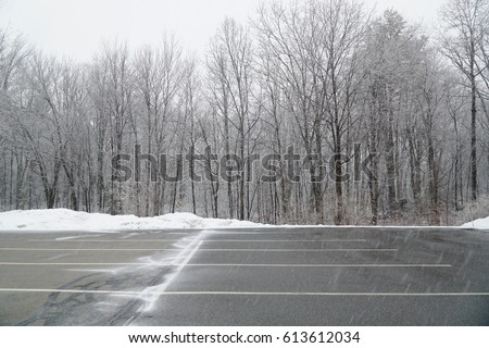empty parking lot with snow removed in front of woods #613612034