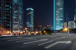 empty pavement and modern buildings in city in night